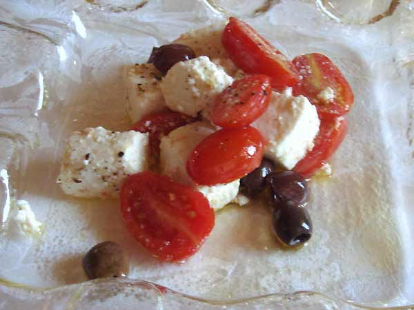 Salad of warm ricotta cheese with cherry tomatoes and olives.