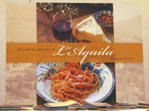 A giant poster shows the cover of 'Breaking Bread in L'Aquila' by Maria Filice.