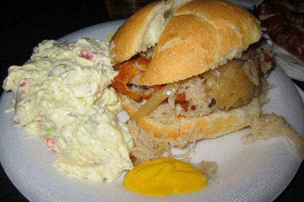 Schnitzel on a bun with saurkraut and sauteed onion and a side of potato salad.
